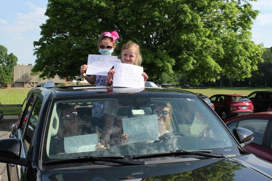 Kenley Farris, 7, and Lucy Farris 5, display their Black Lives Matter signs through their sunroof prior to a protest against racism on Thursday, June 4, in New Canaan. Inside the vehicle are Emily Connair, (passenger), Mary Farris, (driver), and Cecily Farris, 8. Photo: John Kovach / Hearst Connecticut Media / New Canaan Advertiser