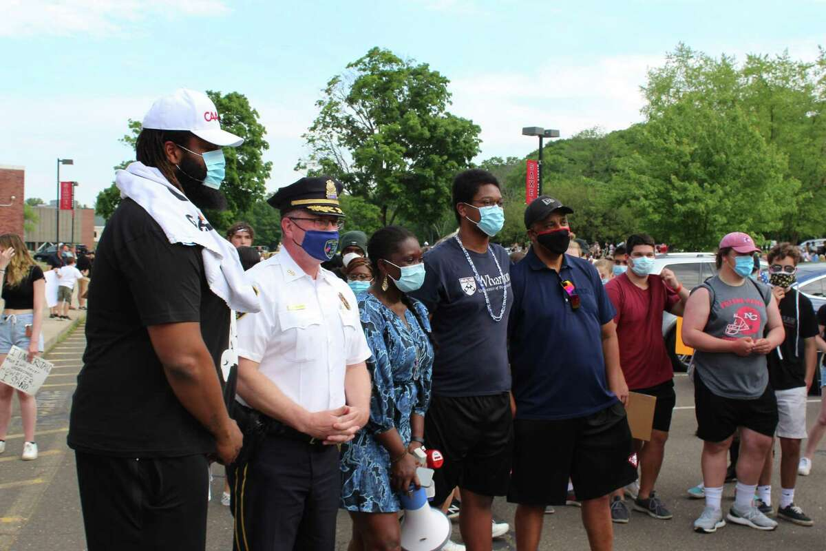 New Canaan Chief of Police Leon Krolikowski poses with members of the Niang family, who organized the march for George Floyd on Thursday, June 4, in New Canaan. Floyd died after a police officer in Minneapolis knelt on his neck for eight minutes and 46 seconds May 25, 2020.