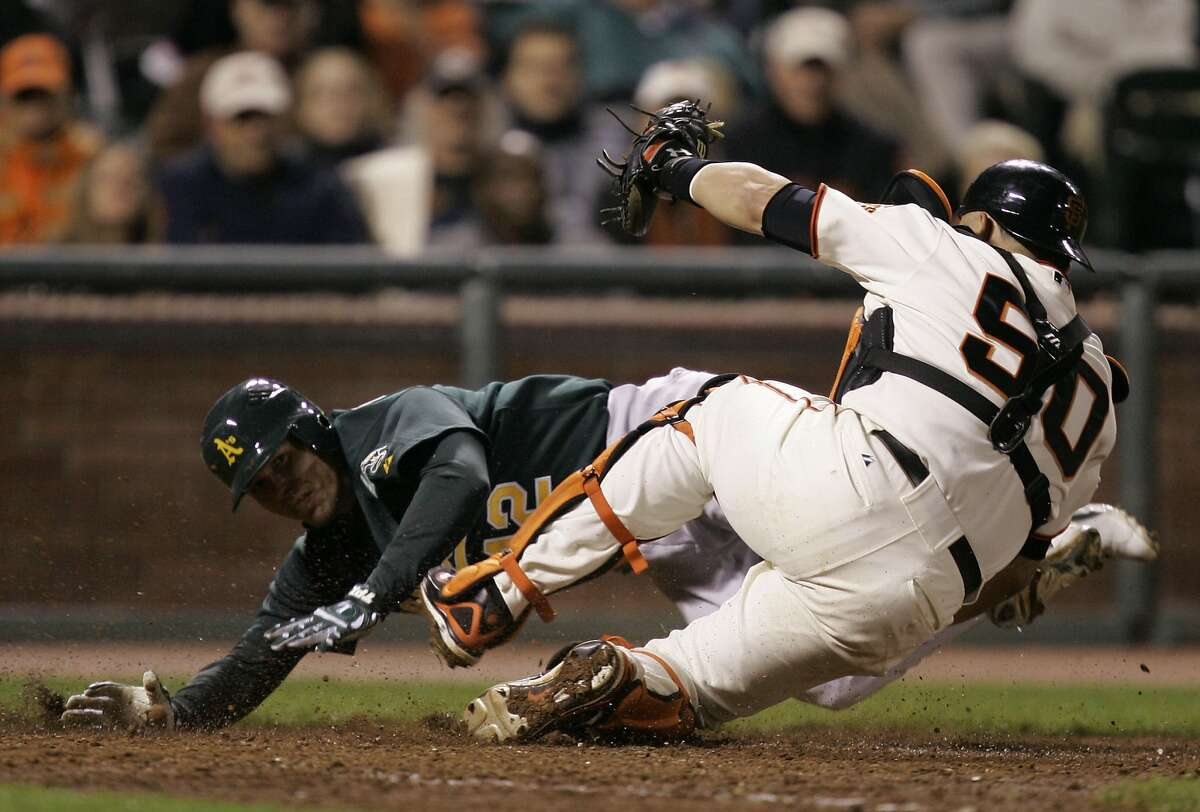Oakland Athletics' Donnie Murphy, left, is tagged out at the plate by San Francisco Giants catcher Eliezer Alfonzo after a throw to the plate from first baseman Ryan Klesko on a ground ball by Mark Kotsay in the 10th inning of a baseball game in San Francisco, Friday, June 8, 2007. Alfonzo had to leave the game after injuring himself on the play. (AP Photo/Marcio Jose Sanchez) Ran on: 06-09-2007 Eliezer Alfonzo (50) topples over after his collision in the 10th inning with the As Donnie Murphy. Alfonzo left with a knee injury.