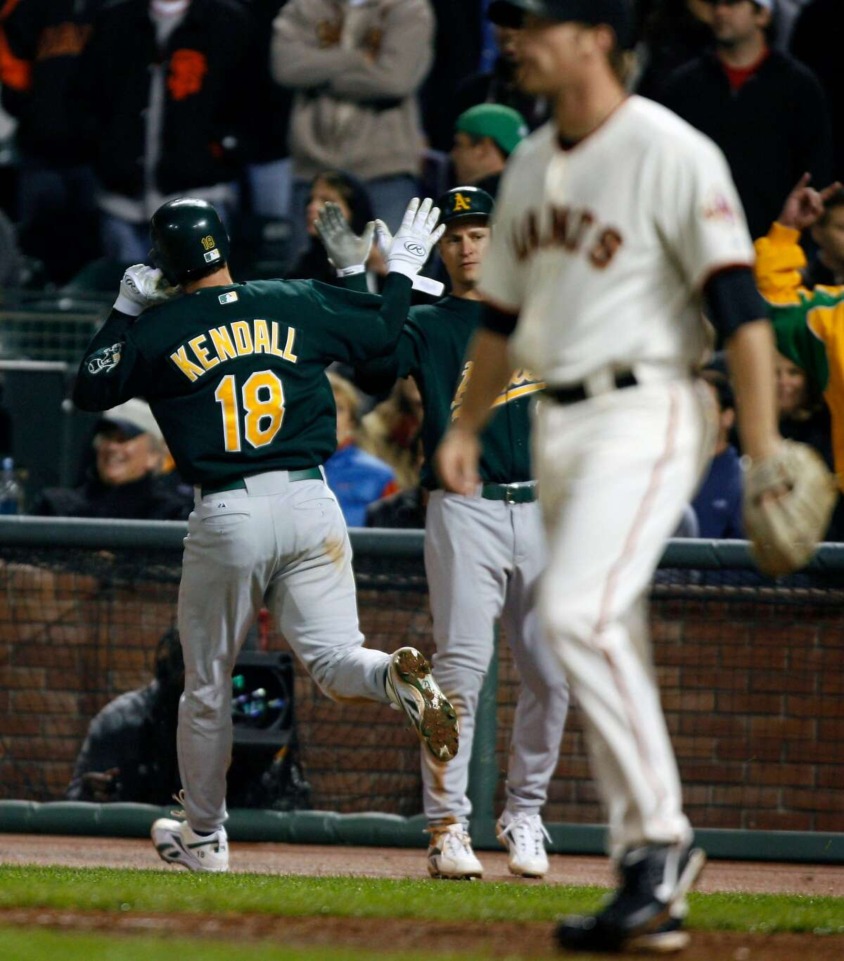 GIANTS_39611.JPG A'S Jason Kindall is greeted after crossing home plate scoring one of two winning runs as they defeated the Giants 5-3. San Francisco Giants vs. Oakland Athletics (June 8) (cq) SUBJECT) Lance Iversen / The Chronicle Photo taken on 6/8/07,in SAN FRANCISCO, CA. Ran on: 06-09-2007 Barry Bonds tells Noah Lowry (right) where to go, while Daniel Ortmeier (left), who had plenty of ground to cover, smiles.