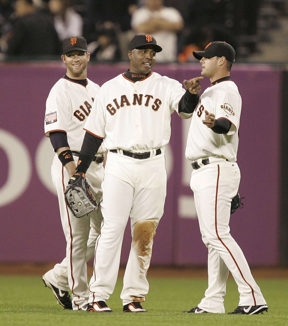 San Francisco Giants pitcher Noah Lowry, right, gets directions from teammate Barry Bonds, center, as Daniel Ortmeier, left, looks on in the 10th inning of a baseball game in San Francisco, Friday, June 8, 2007. Lowry had to take the left field position after the Giants were left out of position players following an injury to catcher Eliezer Alfonzo. (AP Photo/Marcio Jose Sanchez) Ran on: 06-09-2007 Barry Bonds tells Noah Lowry (right) where to go, while Daniel Ortmeier (left), who had plenty of ground to cover, smiles.