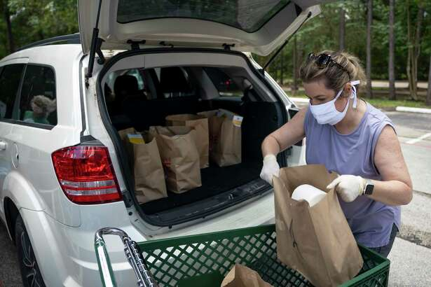 Robin Kitzmiller loads assembled bags of food in the back of a vehicle during a food distribution drive in The Woodlands, Thursday, June 4, 2020.