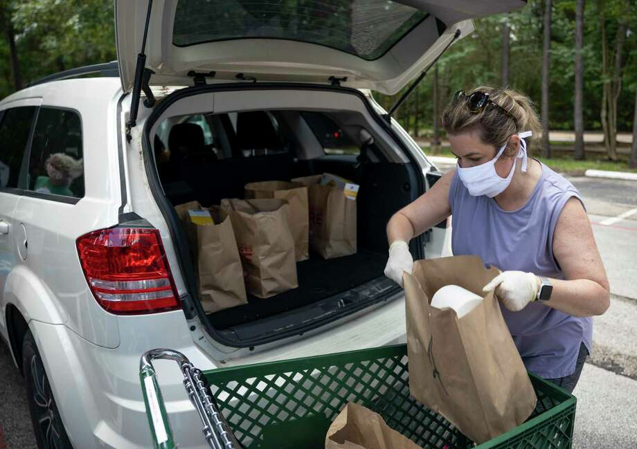 Robin Kitzmiller loads assembled bags of food in the back of a vehicle during a food distribution drive in The Woodlands, Thursday, June 4, 2020. Photo: Gustavo Huerta, Houston Chronicle / Staff Photographer / Houston Chronicle © 2020