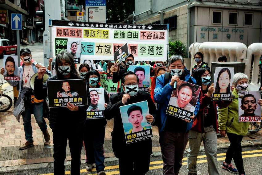Pro-democracy protesters from HK Alliance hold placards of detained rights activists as they march towards the Chinese liaison office in Hong Kong on February 19, 2020, in protest against Beijings detention of prominent anti-corruption activist Xu Zhiyong. - Police in China have arrested Xu Zhiyong, a prominent anti-corruption activist who had been criticising President Xi Jinpings handling of the COVID-19 coronavirus. (Photo by ISAAC LAWRENCE / AFP) (Photo by ISAAC LAWRENCE/AFP via Getty Images)