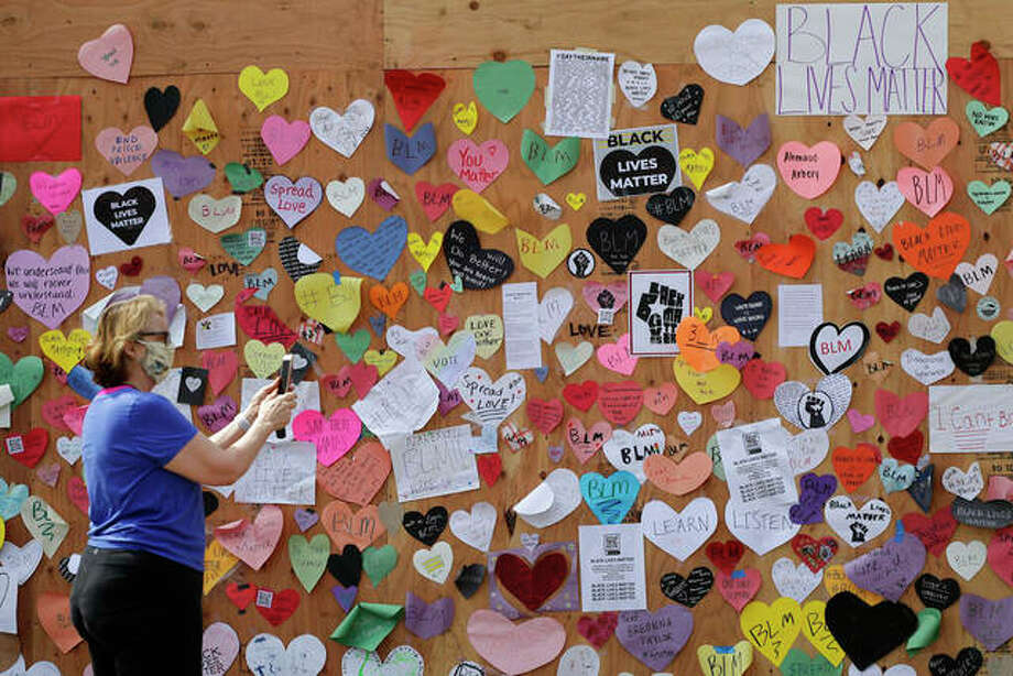 A woman takes photos of the plywood covering the windows of an Apple store in downtown Naperville on Thursday. Residents use hearts and post to send to show they support peace and will not tolerate hate and racism. Photo: Nam Y. Huh | AP