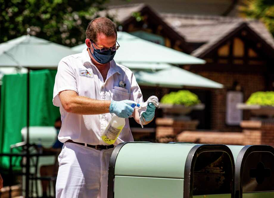 A Walt Disney World employee sanitizes trash receptacles on May 20, 2020, after the reopening of the Disney theme parks that is the largest single employment site in the United States with more than 77,000 workers on the eve of the coronavirus pandemic. (Patrick Connolly/Orlando Sentinel/TNS) Photo: Patrick Connolly / TNS / Orlando Sentinel