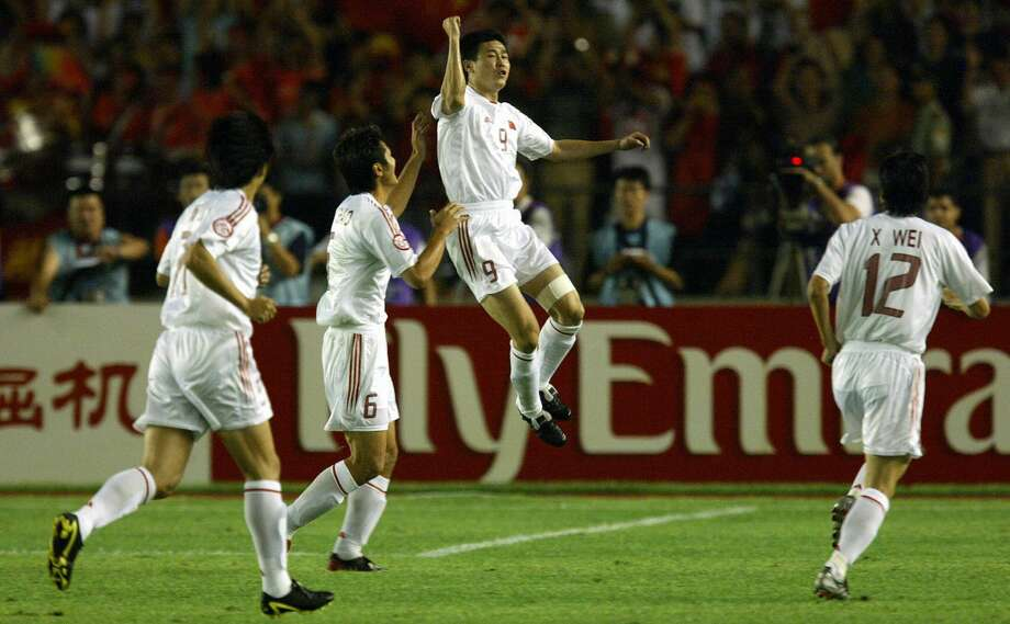 BEIJING, CHINA: China's Hao Haidong (2-R) celebrates his goal with teamates after opening the scoring against Iraq in their quarter-final game in the 2004 Asian Cup Soccer tournament at the Workers Stadium in Beijing, 30 July 2004. Photo: PETER PARKS/AFP Via Getty Images / 2004 AFP