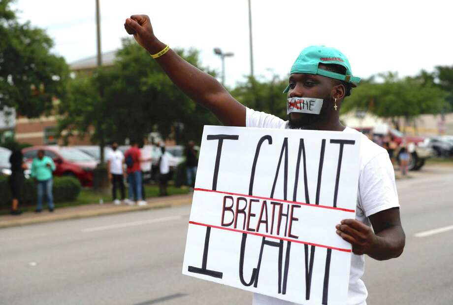 Von Gardner is seen with tape over his mouth while holding his fist into the air as he and others protest the death of George Floyd at Frazier Street and West David Street, Sunday, May 31, 2020, in Conroe. Floyd, originally from Houston, died while he was in the custody of Minneapolis police last week, which has sparked protests throughout the country. Photo: Jason Fochtman, Houston Chronicle / Staff Photographer / 2020 © Houston Chronicle