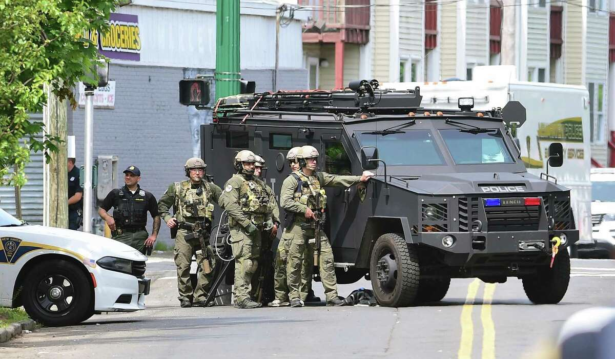 New Haven Police wait behind an armored vehicle in the aftermath of a hostage situation on Henry Street in New Haven on Thursday.
