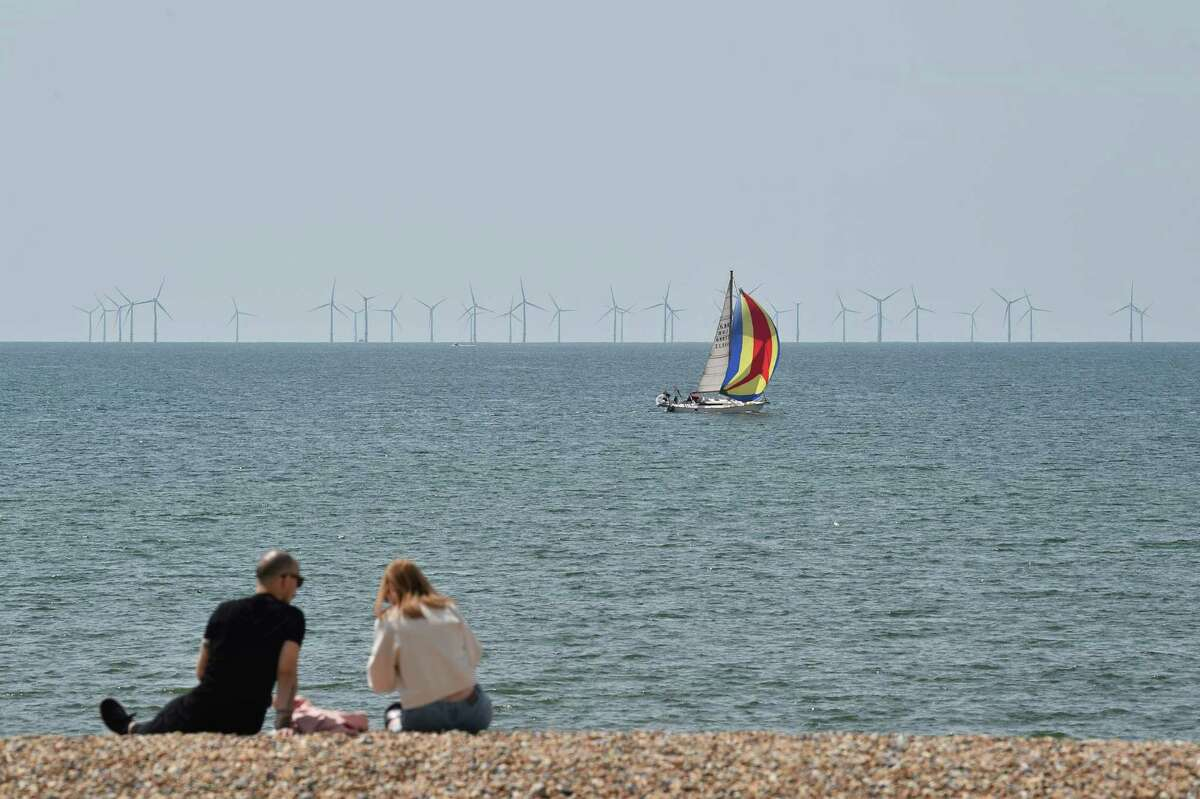 A couple sit watching a boat on the water in front of off-shore wind turbines on the beach in Brighton, southern England, on May 16, 2020.