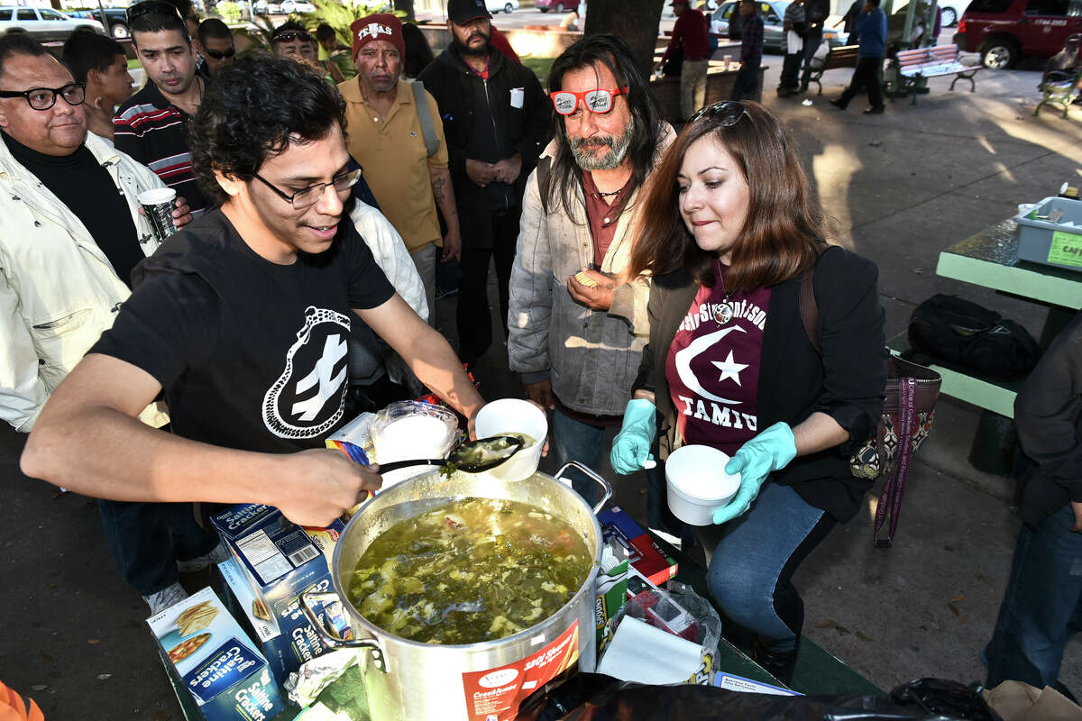 Member of the Laredo Free Thinkers Hector Cubillos and Yasmin Shariff serve a cup of free soup for Johnny Castillo, center, on Saturday afternoon at Jarvis Plaza as the group celebrates one year of community action.