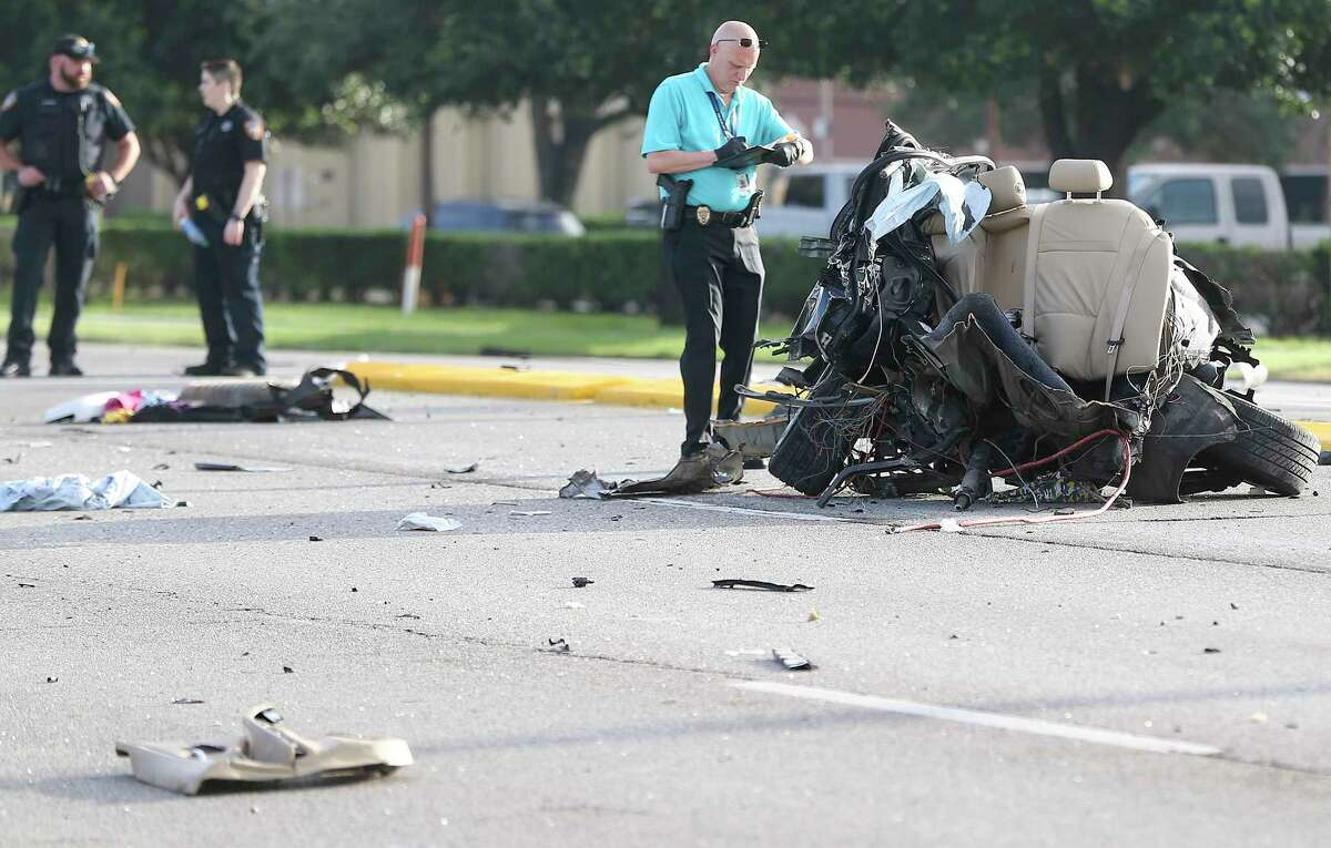 Harris County Sheriff's Department takes a look at the back half of a BMW that split during a fatal accident on Highway 6 in Houston on Friday, June 5, 2020.