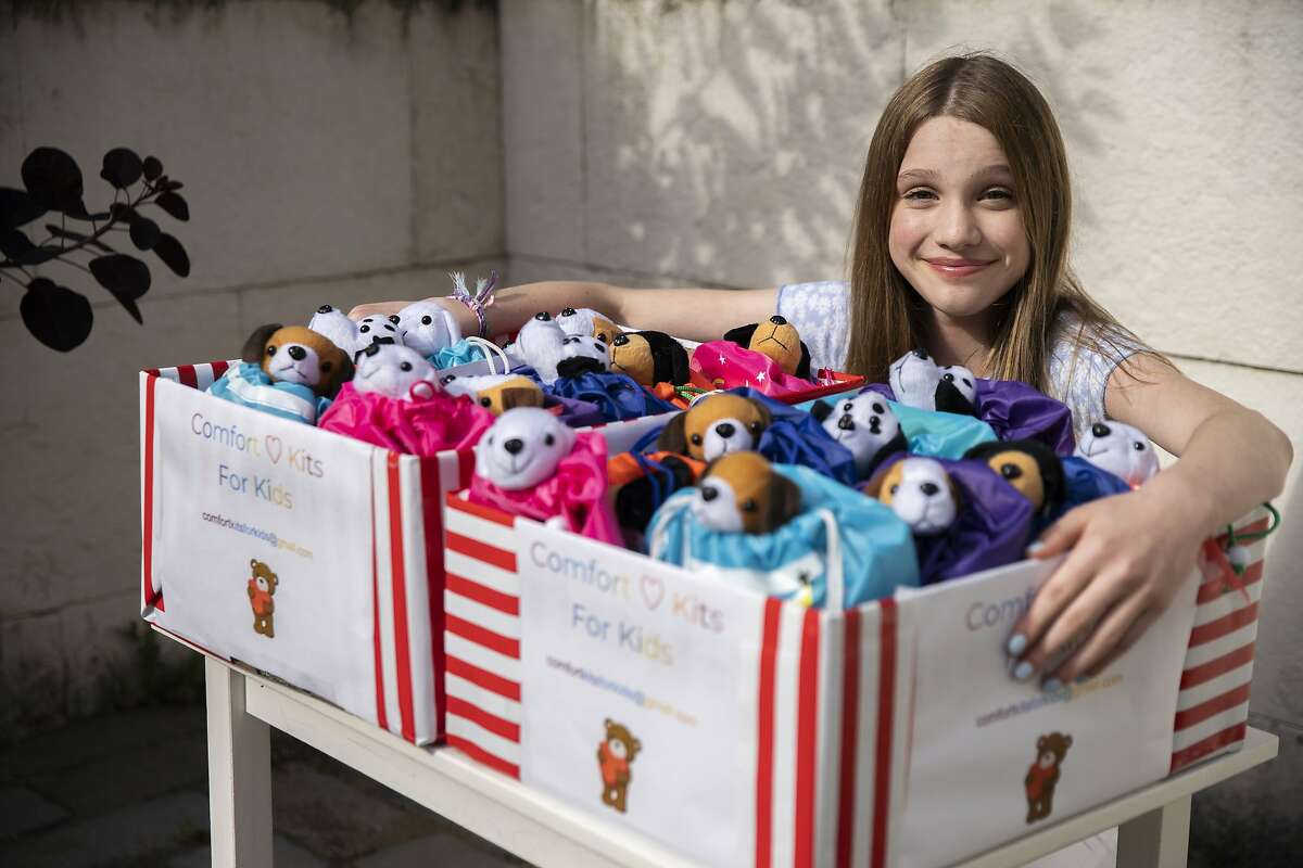 Sadie Cinader with the kits she made on Friday, May 29, 2020, in San Francisco, Calif. Cinader, 13, made kits for kids who have lost loved ones in the pandemic. Each kit has a stuffed animal, stress ball, journal, pen, poetry and a note. She is giving them out to 40 kids who were supposed to go to a special grief therapy camp that got canceled.