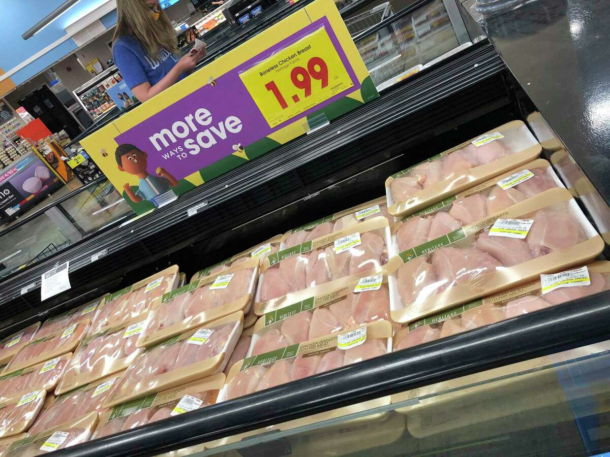 A case filled with packages of boneless chicken breasts is viewed while a shopper, top, in a face mask considers a purchase in a grocery store May 10, 2020, in southeast Denver. The supply chain for meat has run into problems because of the new coronavirus, causing shortages in some parts of the country.