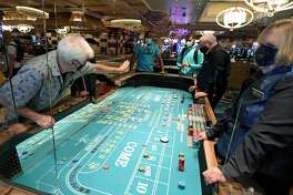 Guests play craps on a table with plexiglass safety shields at Bellagio Resort & Casino on the Las Vegas Strip after the property opened for the first time since being closed on March 17 because of the coronavirus (COVID-19) pandemic on June 4, 2020 in Las Vegas, Nevada. MGM Resorts International is requiring guests to wear masks at all of their craps tables since players have to reach across the gaming area to play.