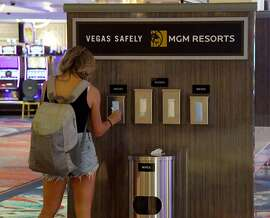 A guest takes a complimentary mask from the side of a new hand-washing station on the gaming floor that also offers gloves and wipes at Bellagio Resort & Casino on the Las Vegas Strip after the property opened for the first time since being closed on March 17 because of the coronavirus (COVID-19) pandemic on June 4, 2020 in Las Vegas, Nevada.