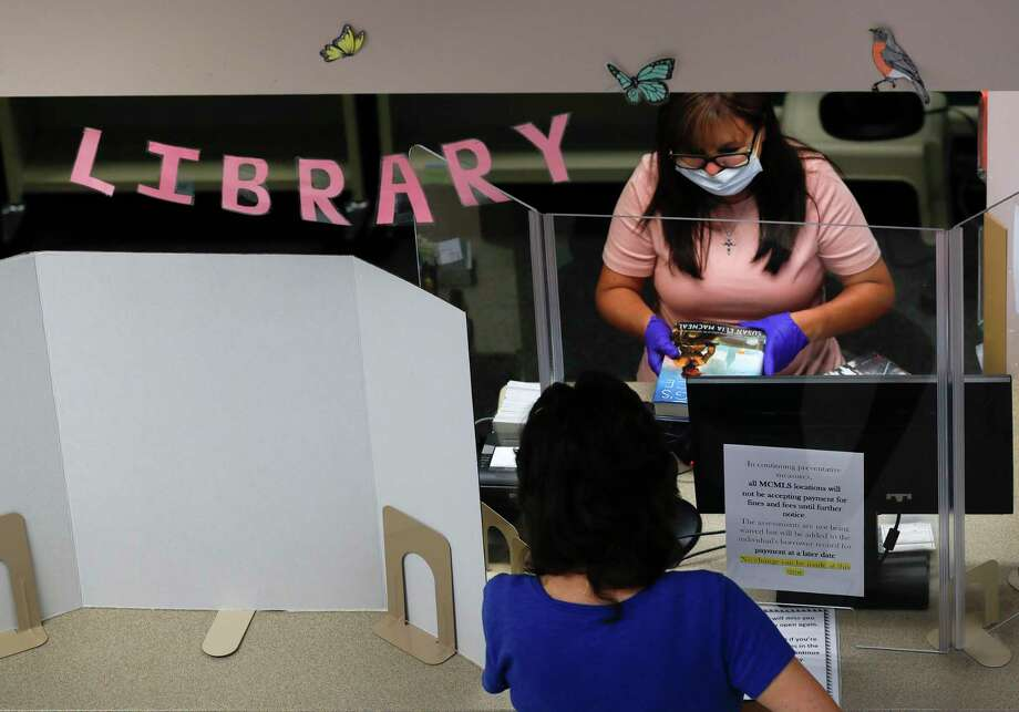 Montgomery County Circulation Coordinator Ruby Chandler scans a book for a visitor as staff with the Montgomery County Central Library reopened to the public, Wednesday, May 13, 2020, in Conroe. The seven county libraries will offer Saturday hours starting this Saturday from 10 a.m. to 2 p.m. Photo: Jason Fochtman, Houston Chronicle / Staff Photographer / 2020 © Houston Chronicle