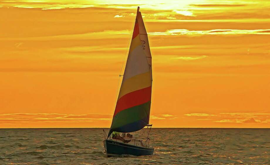 A sailboat cruises at sunset on Saginaw Bay, near the Caseville breakwall. Caseville's Market on Main Street and 37th annual Walleye Tournament will take place as scheduled. (Tribune File Photo)
