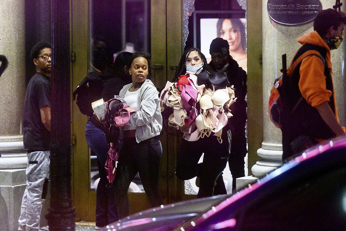 FILE - In this May 30, 2020, file photo, women carry merchandise from a Union Square Victoria's Secret store in San Francisco. Police say many of the smash-and-grab thefts have been carried out by caravans of well-coordinated criminals that have coincided with or followed protests over the death of George Floyd, who was killed by a Minneapolis police officer who pressed his knee into Floyd's neck. (AP Photo/Noah Berger, File)