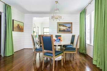 Green linen draperies with blue tape trim dress up the dining room. Interior designer Courtnay Tartt Elias of Creative Tonic loves to mix styles, as she did with the modern dining table and antique reproduction chairs.