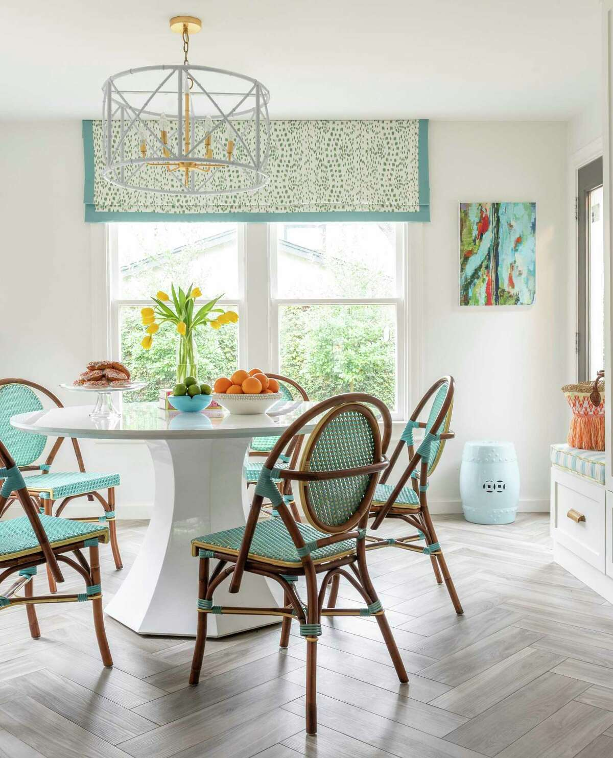 Turquoise and white bistro chairs surround a round white table in the morning room, or breakfast room.