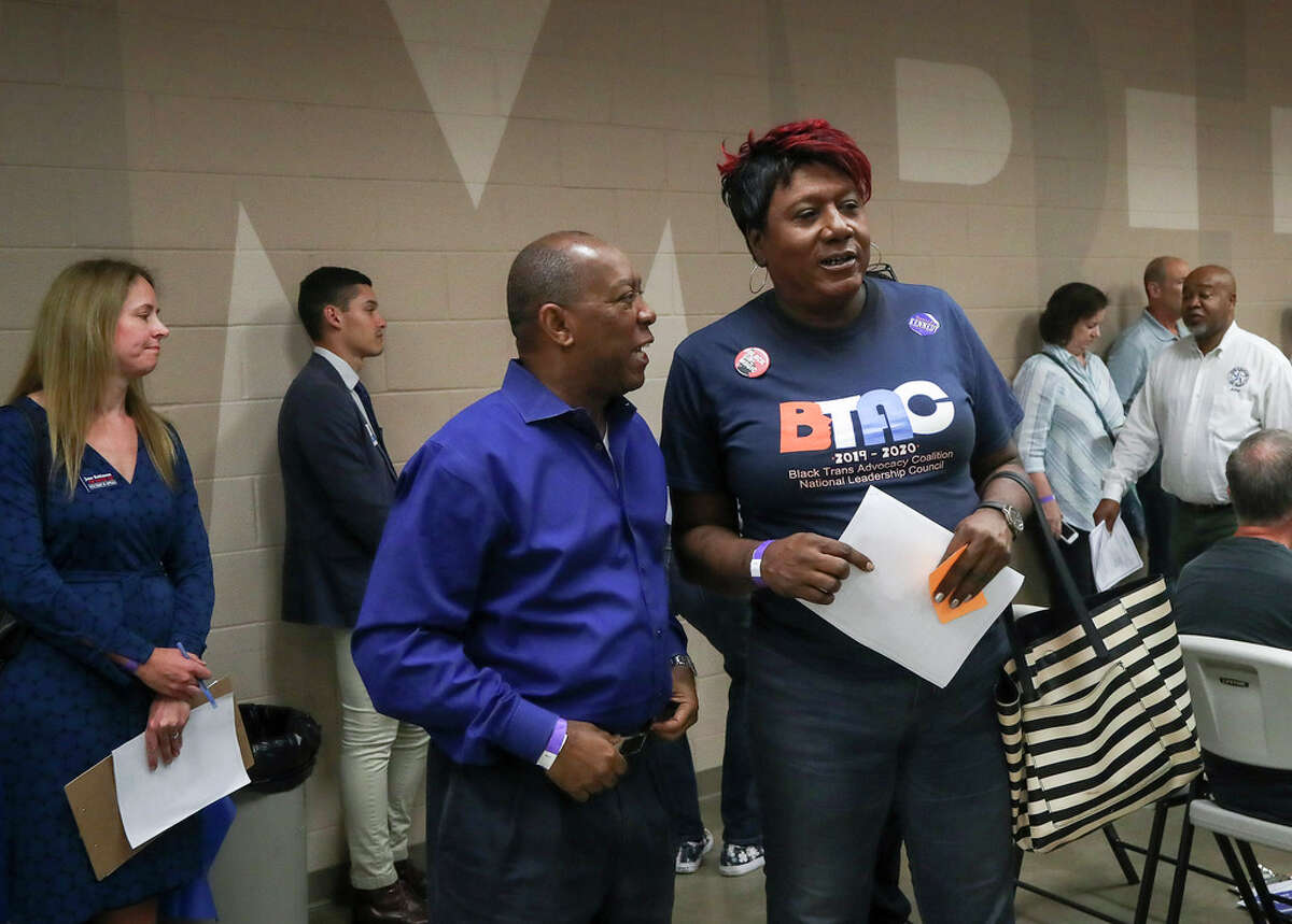 Houston Mayor Sylvester Turner talks with Monica Roberts, who was on Turner's LGBT advisory board, at the Houston GLBT Political Caucus on Saturday, Aug. 3, 2019, in Houston.