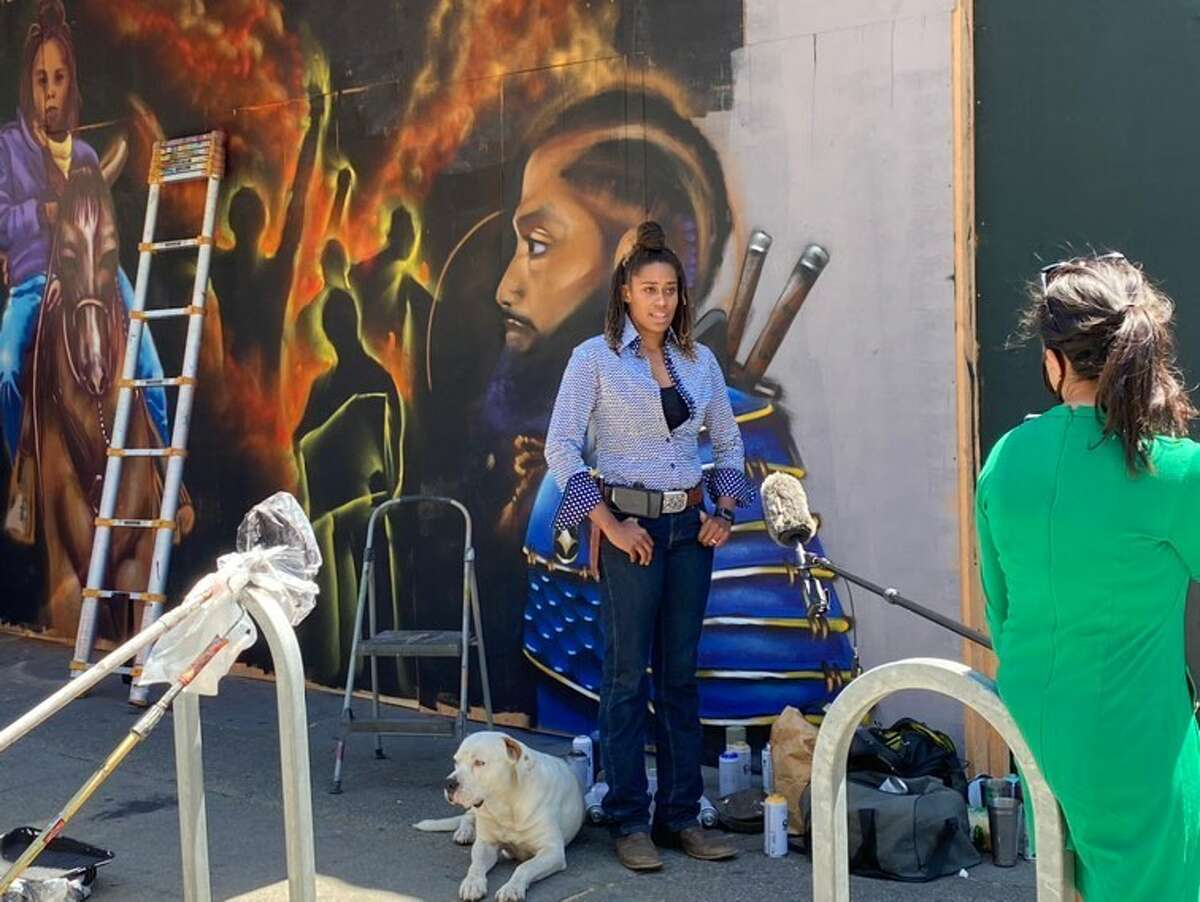 On Thursday, the mural was finished: A fiery scene of shadowed revolutionaries holding fists, signs, and flags to the air, with Brianna Noble on horseback as the centerpiece. A portrait of Nipsey Hussle looks on from the far right of the mural.