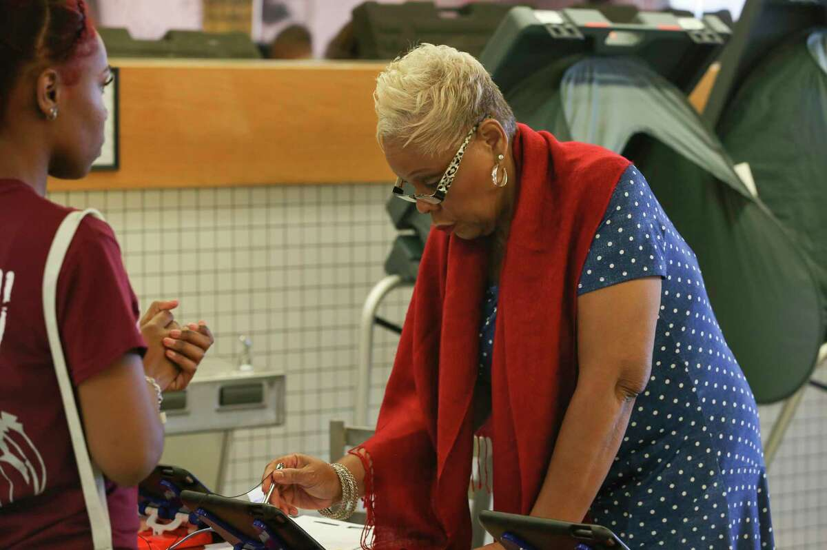 An election official checks in a voter at the Fiesta Mart on Kirby Drive and Old Spanish Trail on Election Day on Tuesday, Nov. 6, 2018, in Houston.