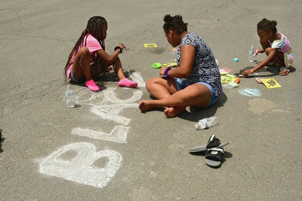 Children write messages with chalk as demonstrators gather in Washington Park for a daily rally against police brutality on Friday, June 5, 2020 in Albany, N.Y. (Lori Van Buren/Times Union)