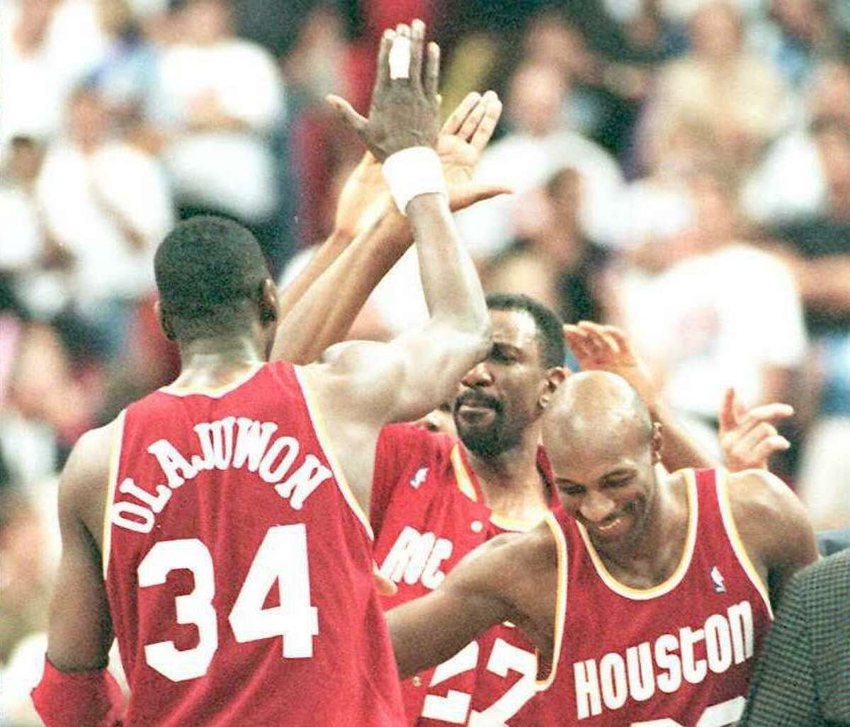 The Rockets' Hakeem Olajuwon gets congratulated by teammates Clyde Drexler (right) and Charles Jones (center) after hitting the game-winning shot in Game 1 of the 1995 NBA Finals on June 7, 1995 in Orlando. The Rockets defeated the Magic 120-118 in overtime.