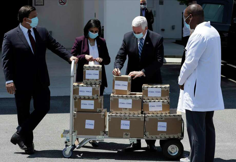 Vice President Mike Pence, second from right, Seema Verma, Administrator of the Centers for Medicare and Medicaid, second from left, and Florida Gov. Ron DeSantis, left, deliver personal protective equipment to a nursing home Wednesday, May 20, 2020, in Orlando, Fla., as part of the initiative to deliver PPE to more than 15,000 nursing homes across America. Photo: Chris O'Meara / Associated Press / Copyright 2020 The Associated Press. All rights reserved.