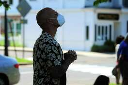 A person participates in a prayer vigil in Milford, Conn., one of many occurring around the country in the aftermath of George Floyd's death death in police custody in Minneapolis. A silent protest and meditation planned in League City aims to accommodate immunocompromised residents.