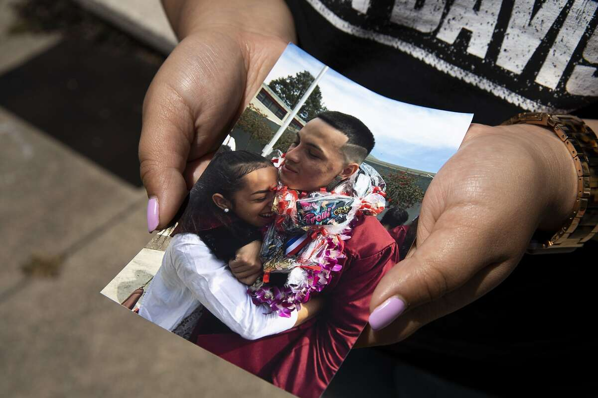 Ashley Monterrosa holds a photo of her hugging her brother Sean Monterrosa at Sean's 2016 graduation, Thursday, June 4, 2020, in San Francisco, Calif.