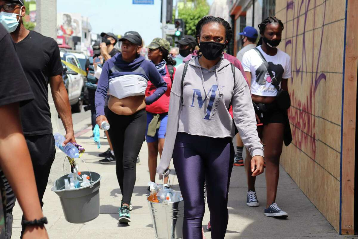People gather to clean a Los Angeles neighborhood after riots les last week. The neighborhood is the unit of change, because residents know how to lift them. They just need the resources.