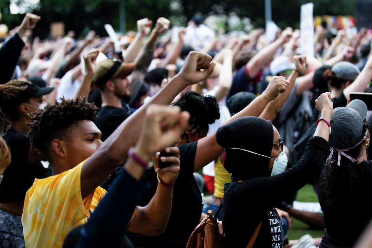 People raise their fists in solidarity of George Floyd's family in a march on Tuesday, June 2, 2020, at the Discovery Green in downtown Houston.