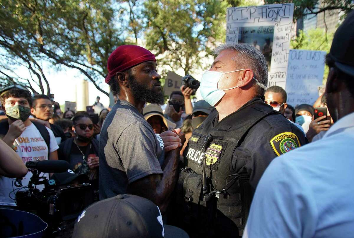 A protester and a Houston Police Officer take a moment after talking following a march and rally with George Floyd's family on Tuesday, June 2, 2020.