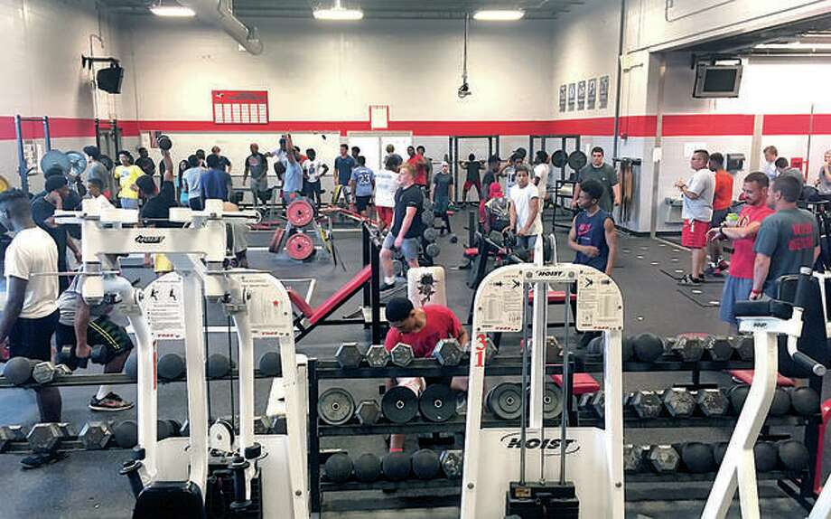 Alton High athletes pack the weight room at Alton High School during a previous summer. The football team, as well as players from other AHS teams, devote many off-season hours to weight training. The IHSA addressed conditioning and weight training in the first stage of its Return to Play plan, which can go into effect Saturday for member schools. Photo: Pete Hayes | The Telegraph