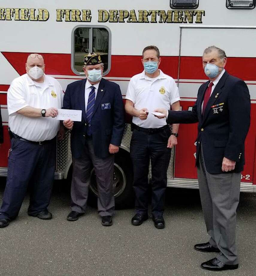 The Marine Veterans of Fairfield County and The Ridgefield American Legion each gave a check for $1,000 to the Ridgefield Fire Departments. Pictured are Fire Chief Jerry Myers; Ridgefield American Legion Commander George Besse; Assistant Fire Chief Michael Grasso; and Dick Tiani of the Marine Veterans of Fairfield County. Photo: Contributed Photo