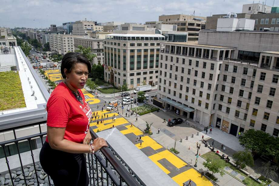 In this image provided by the Executive Office of the Mayor, District of Columbia Mayor Muriel Bowser stands on the rooftop of the Hay Adams Hotel near the White House and looks out at the words 'Black Lives Matter' that have been painted in bright yellow letters on the street by city workers and activists, Friday, June 5, 2020, in Washington. (Executive Office of the Mayor/Khalid Naji-Allah via AP) Photo: Khalid Naji-Allah, Associated Press