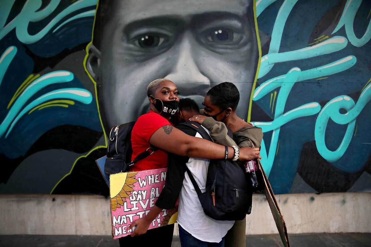 Shan'a Mason, 42, left, hugs her children Aamina Mason, 10, center, and Assata Mitchell, 20, right, as they stand near 14th and Broadway following a protest at Frank Ogawa Plaza in Oakland, Calif., on Thursday, June 4, 2020. The family, who are from San Leandro, attended the event to honor the late George Floyd, a 46-year-old Black man who was killed by a Minneapolis police officer last week.