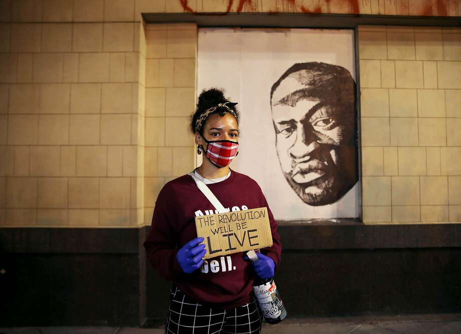 Ailish Elzy, 28, of Oakland, poses for a portrait in front of a George Floyd mural at 14th and Broadway during a George Floyd protest in Oakland, Calif., on Wednesday, June 3, 2020. Floyd, a 46-year-old Black man, was killed by a Minneapolis police officer last week. Elzy is  a grad student at San Francisco State and an Oakland Museum employee. Photo: Yalonda M. James / The Chronicle