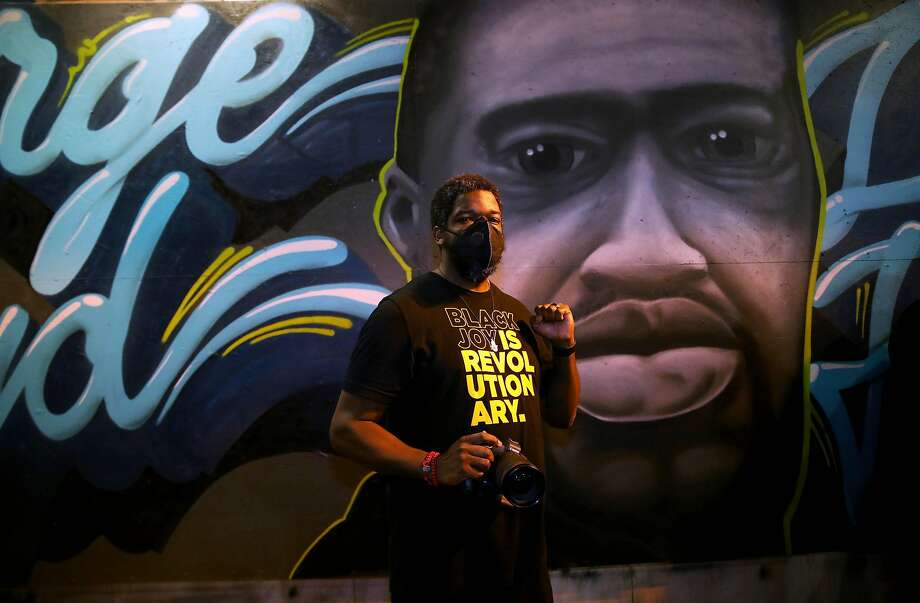 Amir Abdul-Shakur, 37, poses for a portrait with his camera in front of a George Floyd mural at 14th and Broadway during a George Floyd protest in Oakland, Calif., on Wednesday, June 3, 2020. Floyd, a 46-year-old Black man, was killed by a Minneapolis police officer last week. Abdul-Shakur is an Oakland native and a photographer who is also know as Amir the photographer. Photo: Yalonda M. James / The Chronicle
