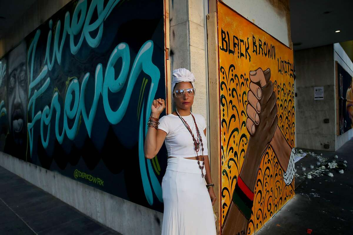 Minerva Arias (left), 38, from Washington Heights in New York City, poses for a portrait between the George Floyd Lives Forever and Black Brown Unity murals after participating in a ceremony at an ancestral altar at 14th and Broadway during a George Floyd protest at Frank Ogawa Plaza in Oakland, Calif., on Thursday, June 4, 2020. Floyd, a 46-year-old Black man, was killed by a Minneapolis police officer last week.