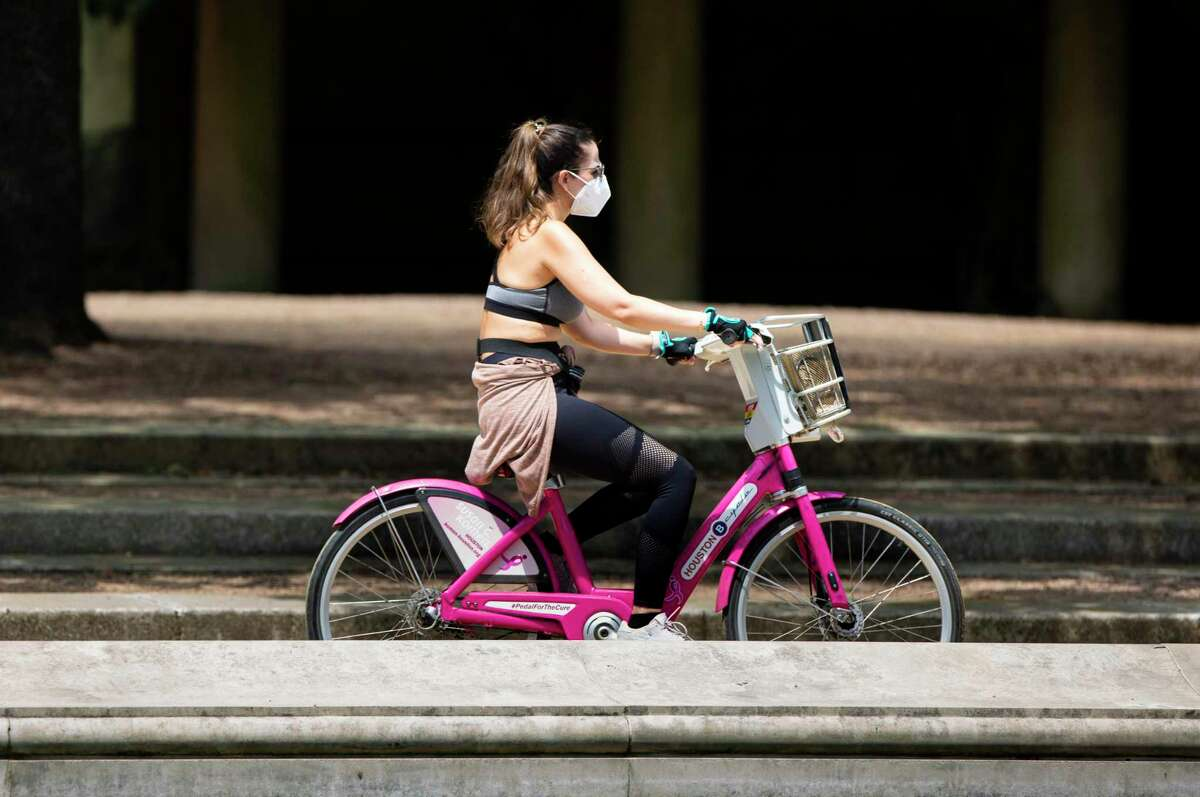 A woman wears a face mask and gloves while riding a Houston BCycle bike during the coronavirus outbreak on May 4, 2020, at Hermann Park in Houston.