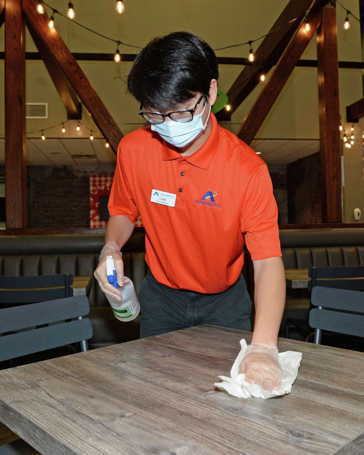 Luke Zhang sanitizes a table at Andretti Indoor Karting & Games, Katy, TX on Thursday, May 28, 2020.