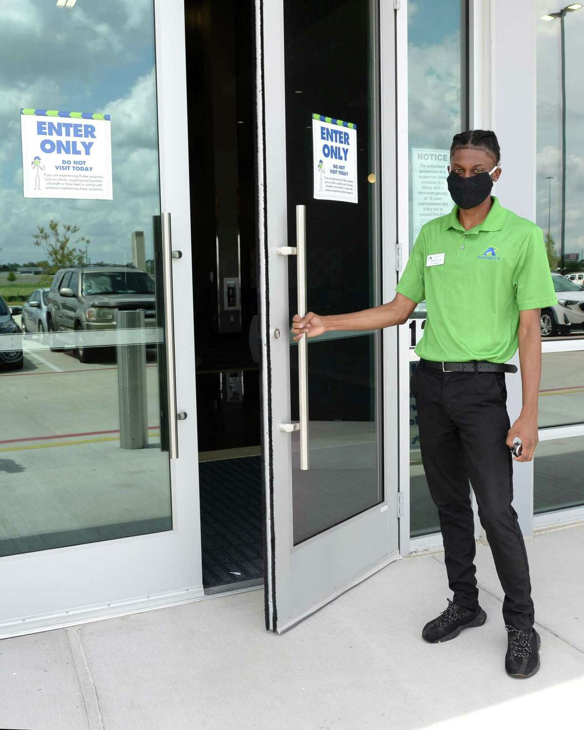 Team Member Toinetee Amos Jr. welcomes guests to Andretti Indoor Karting & Games, Katy, TX on Thursday, May 28, 2020. Entrances and exits are marked for one-way traffic flow.