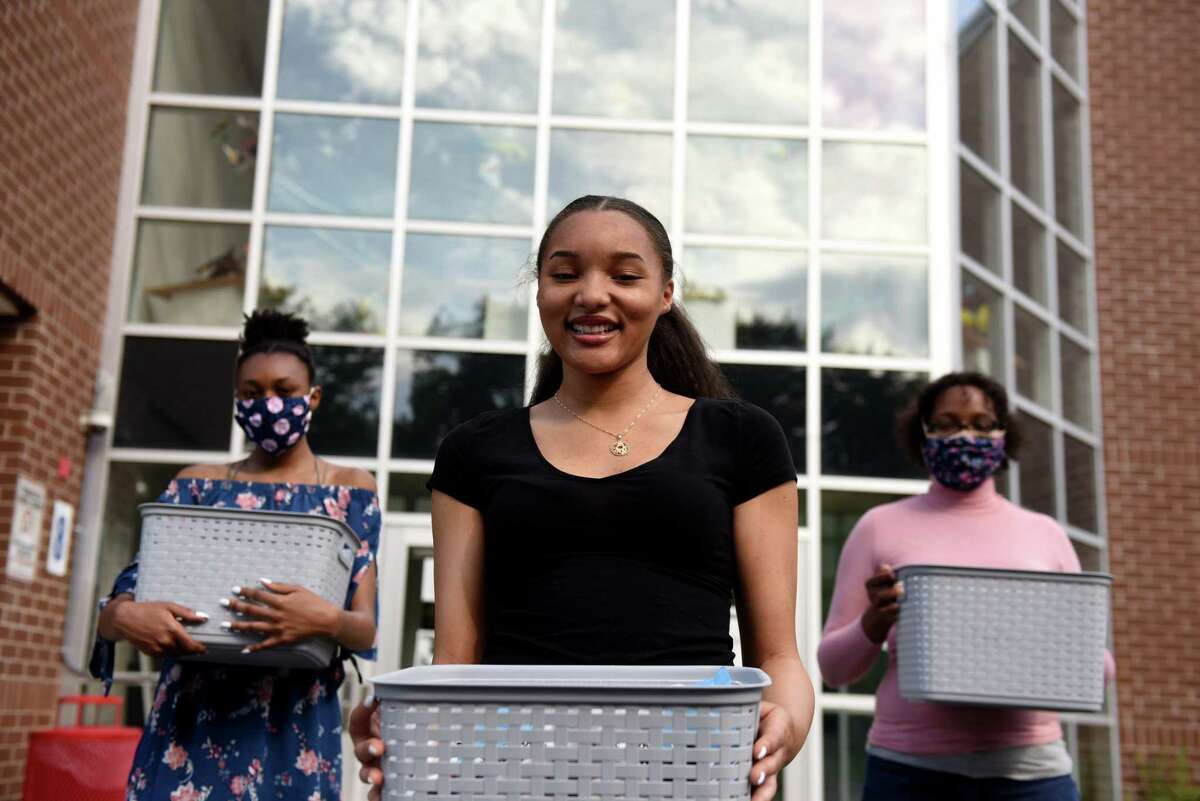 Graduating Schenectady High School senior Kini-Analysa McCalmon, center, is pictured with her sister, Zilya, 14, left, and mother, Thearse McCalmon, right, on Thursday, June 4, 2020, in Schenectady, N.Y. Kini-Analysa made face masks and assisted her community in overcoming coronavirus hardships. (Will Waldron/Times Union)