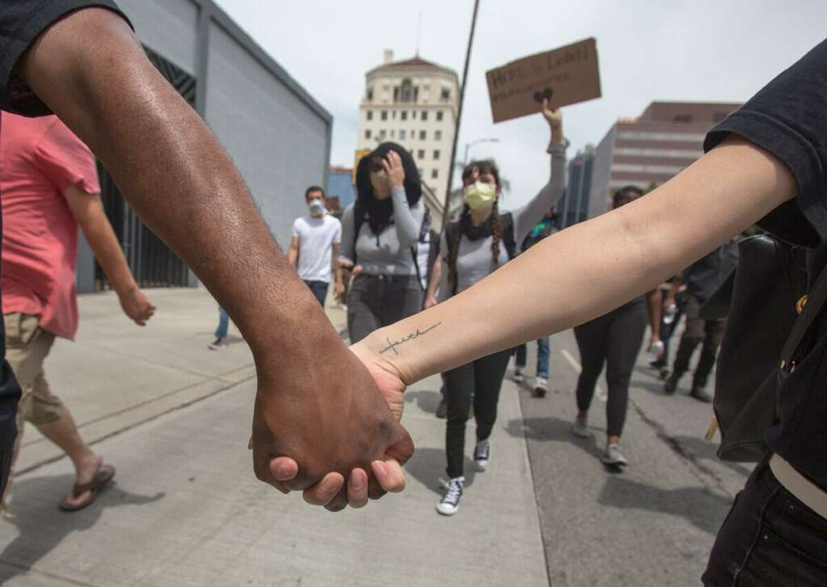Demonstrators hand in hand march during a protest Tuesday in Hollywood, a section of Los Angeles, over the death of George Floyd in Minneapolis.