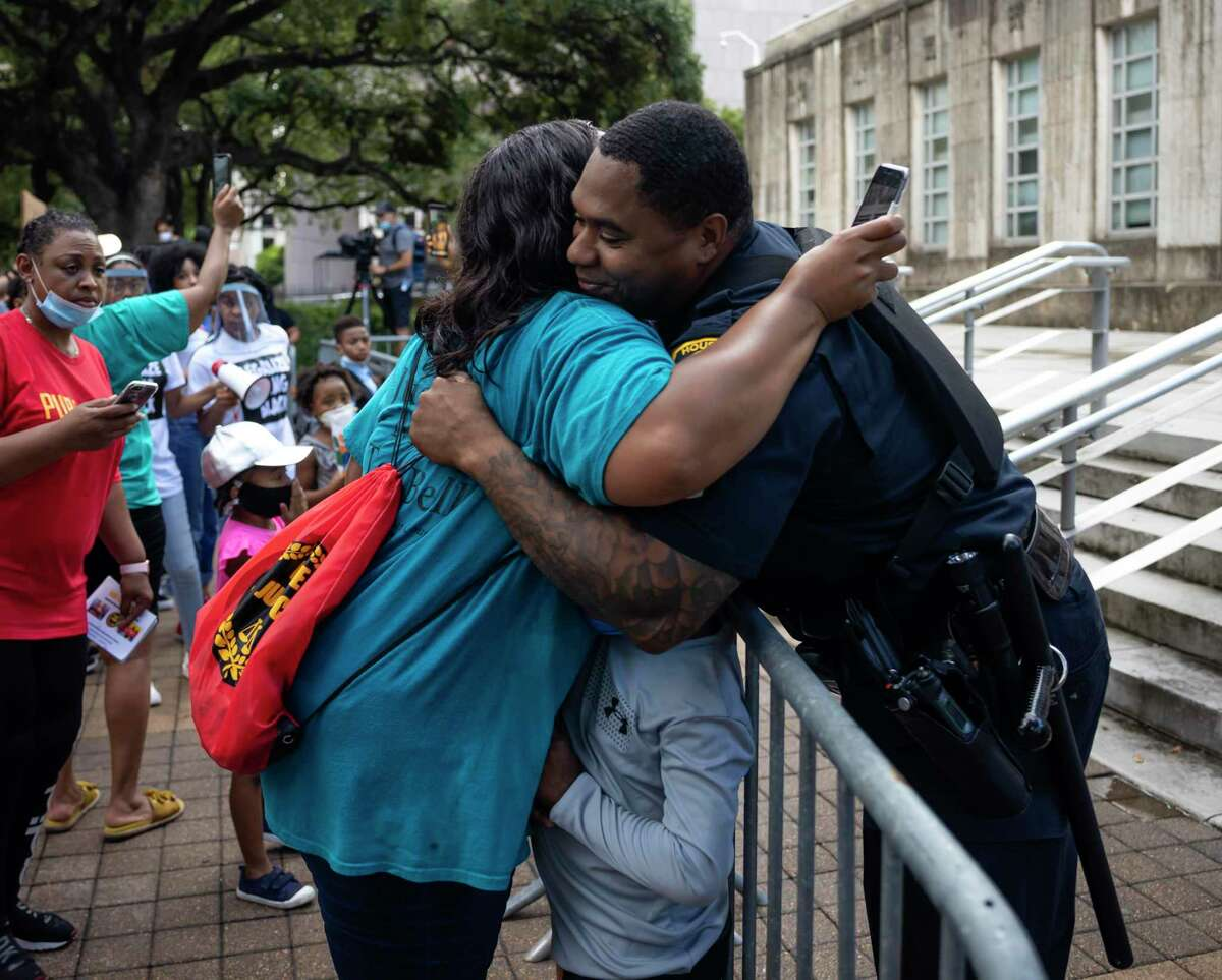 A Houston Police Department officer and a demonstrator hug during a candle light vigil in honor of George Floyd who's death sparked protests throughout the country, Thursday, June 4, 2020.