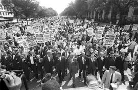 """(FILES) US civil rights leader Martin Luther KIng (3rd from L) walks with supporters during the """"March on Washington"""" 28 August, 1963 after which, King delivered the """"I Have a Dream"""" speech from the steps of the LIncoln Memorial. 28 August, 2003 marks the 40th anniversary of the famous speech, which is credited with mobilizing supporters of desegregation and prompted the 1964 Civil Rights Act. King was assassinated on 04 April 1968 in Memphis, Tennessee. James Earl Ray confessed to shooting King and was sentenced to 99 years in prison.  AFP PHOTO/FILES  (Photo credit should read -/AFP/Getty Images)"""